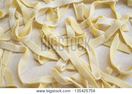 fresh homemade egg tagliatelle on a pastry board