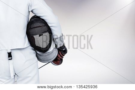 Rear view of swordsman holding fencing mask and sword against grey background
