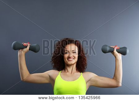 Attractive woman exercising with dumb bells on grey background