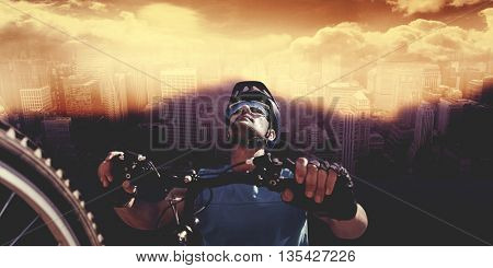 Man cycling with mountain bike against aerial view of a city on a cloudy day