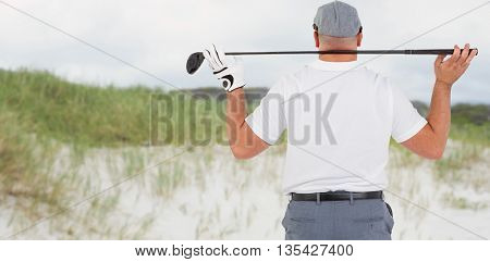 Rear view of golf player holding a golf club against view of sand