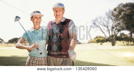 Couple golf players looking the camera against view of a park