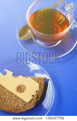 A cup of tea and a cheese sandwich on a blue tray
