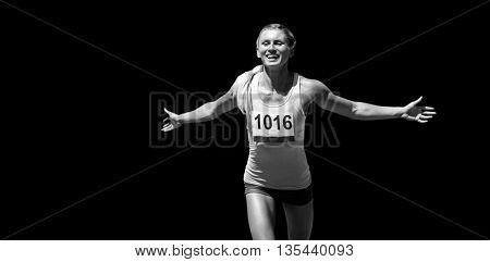 Sportswoman finishing her run against black background