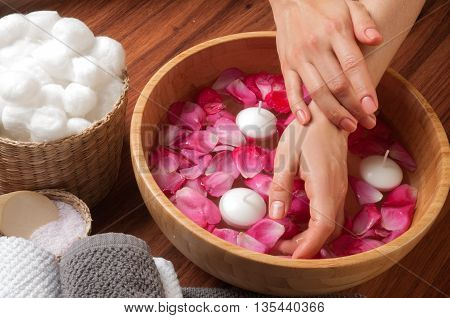 Female hands in bowl of spa water with flowers hand care in nail salon relaxing manicure with a pink rose flower