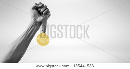Hand holding a silver medal on white background