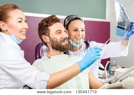 Dentist Shows A Patient X-ray Of Teeth.