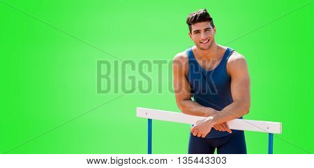 Portrait of sportsman is smiling and posing on a hurdle against green background