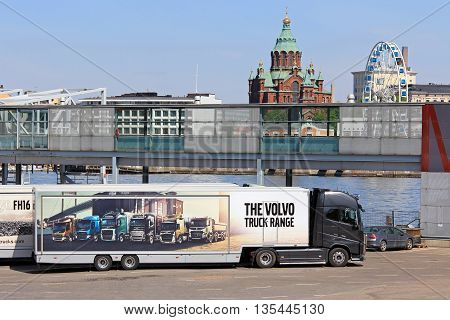 HELSINKI, FINLAND - MAY 24, 2016: Volvo FH16 750 semi parked at Olympic terminal Helsinki shows the Volvo truck range pictured on trailer with Uspenski Cathedral and SkyWheel Helsinki on the background.