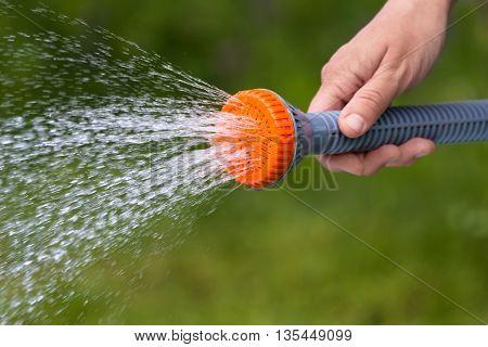 hand watering garden with sprinkler on blurred background closeup
