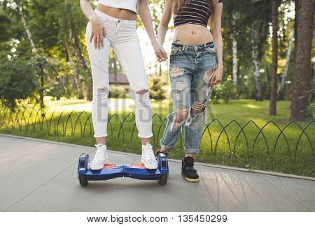 Two Young sexy fit woman in jeans riding hoverboard - electrical scooter, personal eco transport, gyro scooter, smart balance wheel. Summer photo. Blurred background..