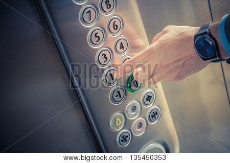 Male finger pressing the first floor button in the elevator
