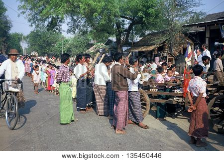 PAGAN / MYANMAR - CIRCA 1987: Men play musical instruments while children march in a Buddhist parade in Pagan during a holiday.