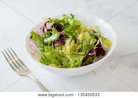 Mixed fresh vegetable salad (green iceberg lettuce radicchio and frisee) in white bowl on a white background