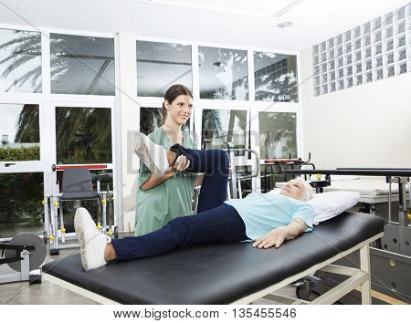 Nurse Assisting Senior Woman In Leg Exercise At Rehab Center