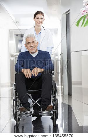 Female Doctor Pushing Senior Patient In Wheel Chair