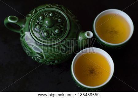 Two cups of green tea and traditional chinese tea pot for tea ceremony view from above