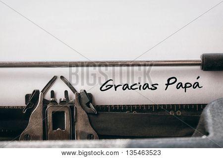 Word gracias papa against close-up of typewriter