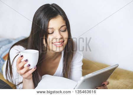 Enjoying her new digital tablet. Beautiful young woman holding touch pad and looking at it with smile. Woman at home relaxing on sofa couch reading email on the tablet computer