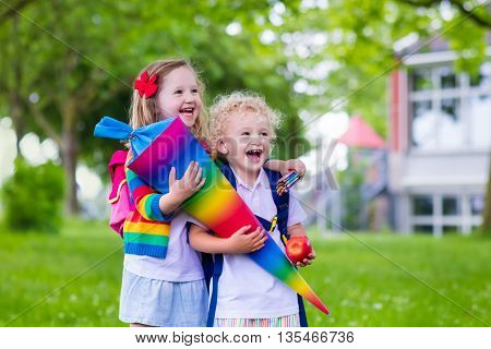 Child going to school. Boy and girl holding traditional candy cone on the first school day. Little students with books excited to be back to school. Beginning of class in Germany with sweets for kids.