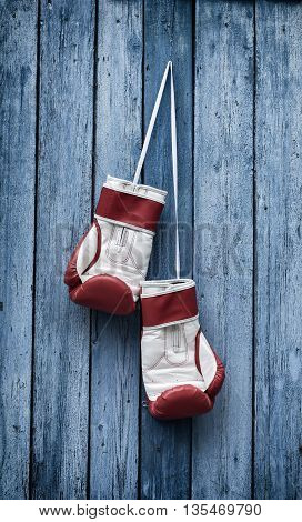 Boxing gloves hang on the old blue wooden wall from a nail