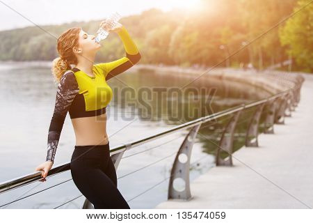 Caucasian woman in sportswear drinking water after sport. Image with lensflare