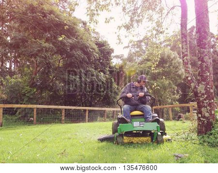 A baby boomer is mowing grass on a rural property on a ride on lawn mower. Filtered image for a vintage retro look with lens flare and grain.