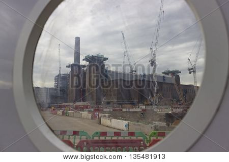 London England - May 22 2016: Construction cranes over the Battersea power station currently being rebuilt and transformed into luxury housing shops and entertainment in London England.
