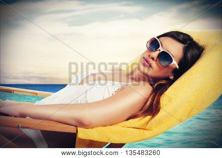 Woman lying on a deckchair with sea on background