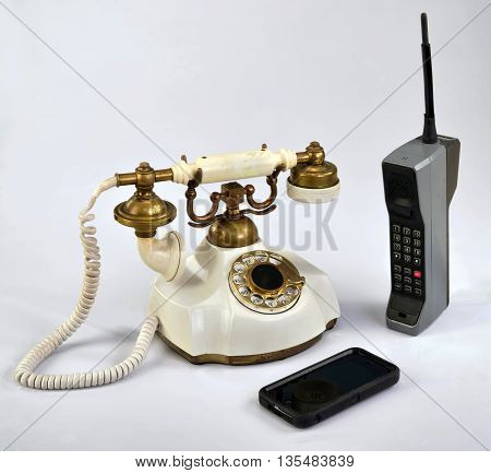 Working smart cell phone and old white rotary telephone.