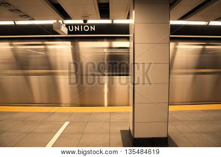 A fast moving subway whizzing by at an underground subway platfrom