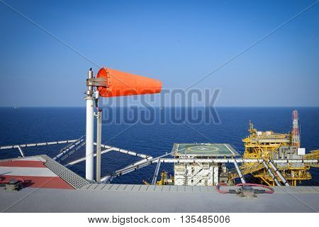 The wind sock is set on the oil rig to showing wind direction for helicopter landing .