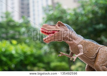 gigantic tyrannosaurus stands in front of trees and morden building