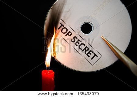 burning a top secret compact disc with candle in dark