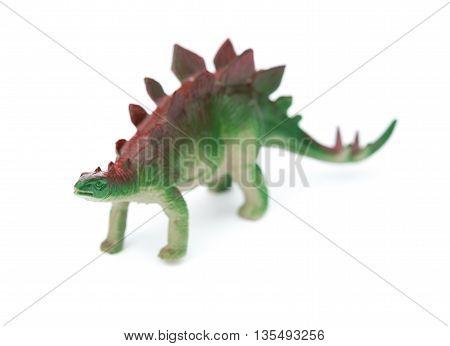 green stegosaurus toy on a white background