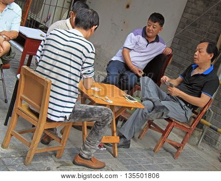 Wuhan, China - June 22, 2015: men are playing cards outdoor in Wuhan, China