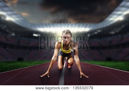 Composite image of sportswoman in the starting block in a stadium