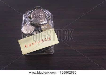 Finacial concept. Money in the glass on wooden table with business word and copy space area.