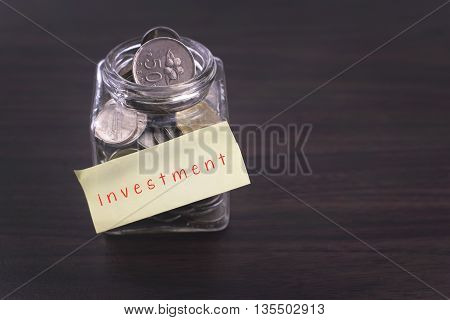 Finacial concept. Money in the glass on wooden table with investment word and copy space area.