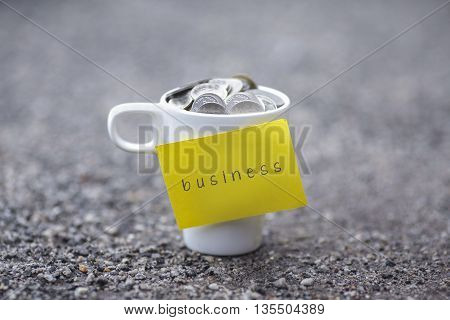 Coins in mug with business label blurred at background. Financial concept.