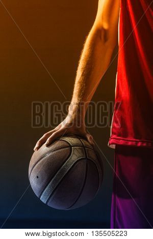 Close up on basketball held by basketball player on a gym