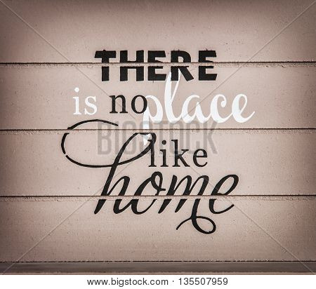 There is no place like home. Title on the wooden background. Symbolic inscription.