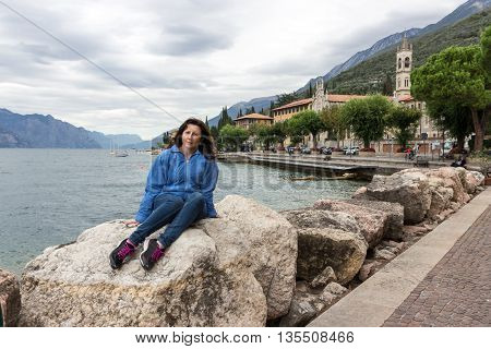Woman sitting on a stone at the shores of Lake Garda near Castelletto Italy