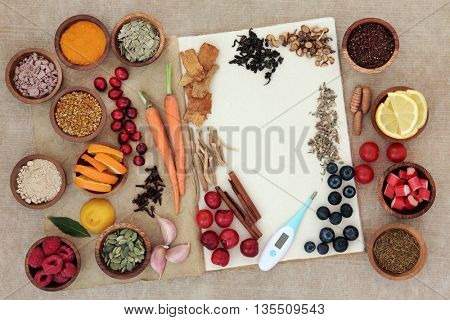 Food selection for cold and flu cure to boost immune system with thermometer, high in vitamins, anthocyanins, antioxidants and minerals in wooden bowls over white background.