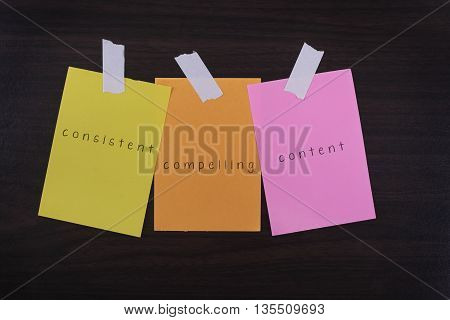 Word quotes of consistent compelling content on sticky color papers against wooden textured background.