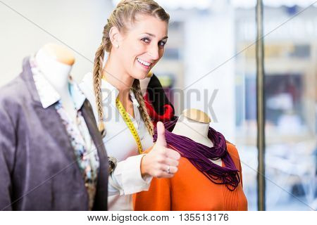 Small business owner dressing shop window putting new fashion clothes on mannequin