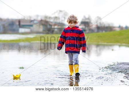 Beautiful little kid boy in rain boots playing with paper boat by a puddle on warm spring day. Active leisure for children. Child having fun outdoors.