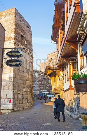 ANKARA TURKEY - JANUARY 16 2015: The narrow tourist street of the Turkish village with the tiny stalls and cozy cafes adjacent to the medieval fortress ramparts on January 16 in Ankara.