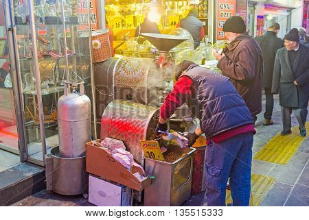 ANKARA TURKEY - JANUARY 16 2015: The seller pours the chickpeas cooked in the roasting machine in the street next to the Suluhan Market on January 16 in Ankara.