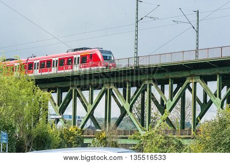 ESSEN KETTWIG NRW GERMANY - APRIL 28 2016: Express train crossing the railway bridge in Essen Kettwig an der Ruhr in Germany. By powered express train toward Duesseldorf.